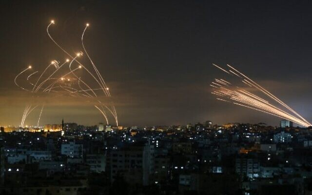 """Rockets are seen in the night sky fired towards Israel from Beit Lahia in the northern Gaza Strip on May 14, 2021. - Israel bombarded Gaza with artillery and air strikes on Friday, May 14, in response to a new barrage of rocket fire from the Hamas-run enclave, but stopped short of a ground offensive in the conflict that has now claimed more than 100 Palestinian lives. As the violence intensified, Israel said it was carrying out an attack """"in the Gaza Strip"""" although it later clarified there were no boots on the ground. (Photo by ANAS BABA / AFP)"""